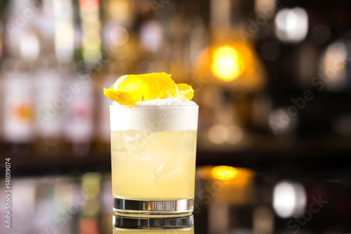 Fotografia Closeup glass of whiskey sour cocktail decorated with lemon at bar background