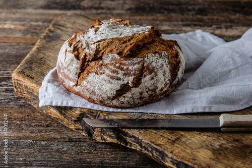 Leinwand Poster Frisches rundes Brot auf einem Holzbrett