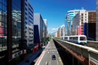 View of a train traveling on elevated tracks of Taipei Metro System between office towers under blue clear sky ~ View of MRT railways in Taipei, the capital city of Taiwan, on a beautiful sunny day