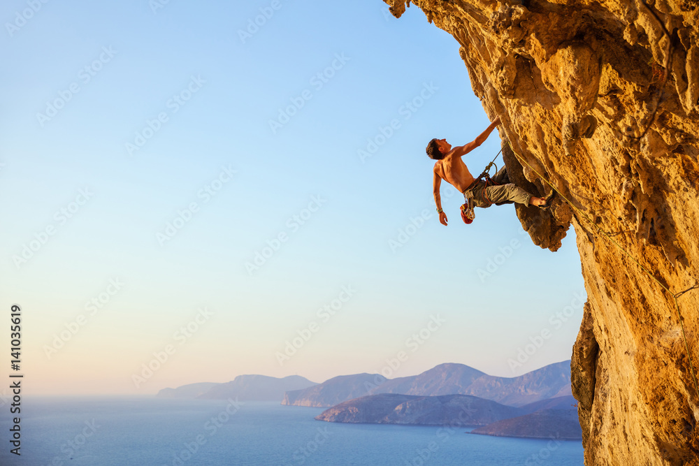 Fototapety, obrazy: Rock climber on cliff at sunset