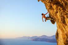 Rock Climber On Cliff At Sunset