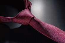 Tied Red A Tie On A Dark Table.