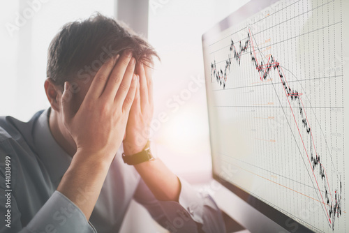 Fotografía Frustrated stressed shocked business man with financial market chart graphic going down on grey office wall background