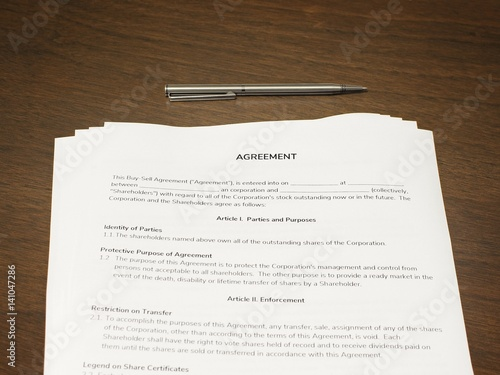 Contract Papers With A Pen On The Wooden Table The Documents Is