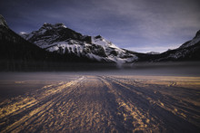 Snow Capped Mountains And Snow Covered Landscape At Sunset