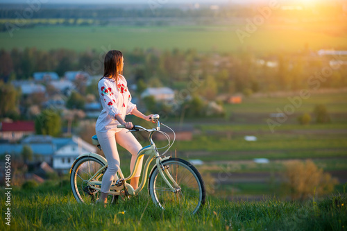 Woman with retro bike on the hill in the evening Wallpaper Mural