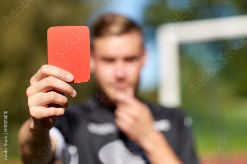 referee hands with red card on football field Fototapet