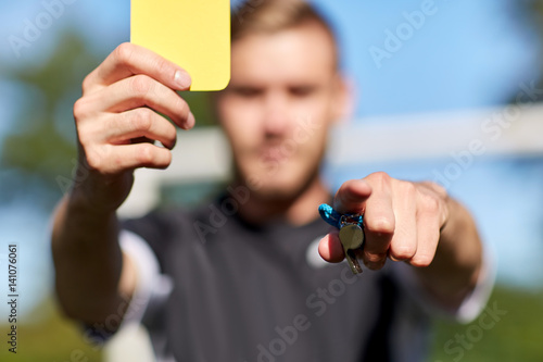 Fotografering  referee on football field showing yellow card