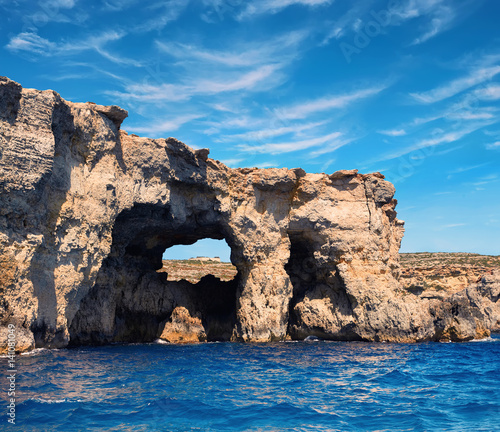 Limestone rock caves and blue Mediterranean water of Comino