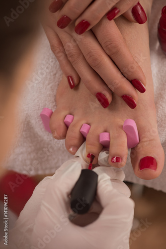 Poster Pedicure female feet and hands at spa salon