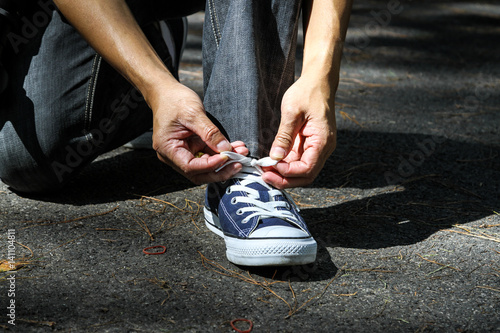 Man tighten or laces the shoes