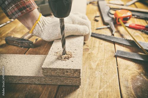 Carta da parati Man drills the wooden plank