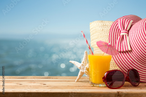 Photo  Summer holiday vacation concept with orange juice, hat and sunglasses over sea b