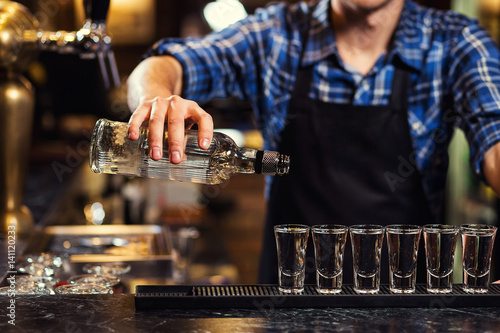 Fotografia Barman at work,Barman pouring hard spirit into glasses in detail,Bartender is po