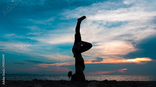 Poster Yoga school Silhouette of a woman playing yoga on twilight. Sunset sky background