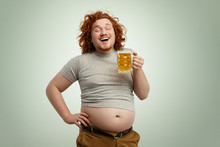 Happy Joyful Young Overweight Man With Curly Red Head Closing Eyes In Enjoyment, Anticipating First Gulp Of Cold Frothy Beer, Holding Glass Of Beverage In Hands, His Belly Hanging Out Of Pants
