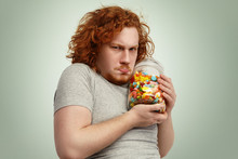 Obese Chubby European Man With Ginger Curly Hair Holding Jar Of Sweets Tight, Having Greedy Look, Frowning And Grimacing, Posing Indoors At Studio Wall. Obesity, Gluttony And Unhealthy Lifestyle