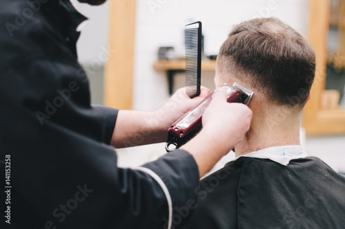 Haircut men Barbershop. Men's Hairdressers; barbers. Barber cuts the client machine for haircuts.