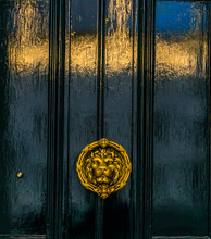 Beautiful Brass Knocker In The Shape Of A Lion's Head On A Background Of The Black Wooden Door, Echoing The Shape Of The Building On The Door