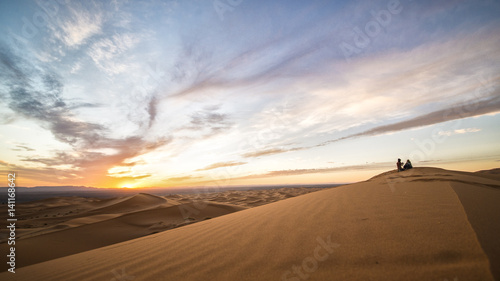 Papiers peints Route 66 A couple enjoying the sunset on the dunes of the Sahara Desert in Merzouga - Morocco