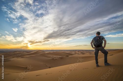 Cadres-photo bureau Desert de sable Man walking alone on the dunes of the Sahara Desert in Merzouga admiring the sunset - Morocco