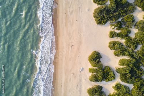 Fotografía  View from above, stunning aerial view of a beautiful and uncontaminated wild beach bathed by a rough sea during the sunset
