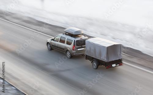 Zdjęcie XXL Samochód z przyczepą jeździ po zimowej drodze