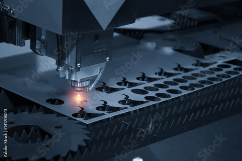 Fotografie, Obraz  The CNC laser cut machine while cutting the sheet metal with the sparking light