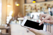 Woman using touch screen mobile phone with Coffee shop blur background