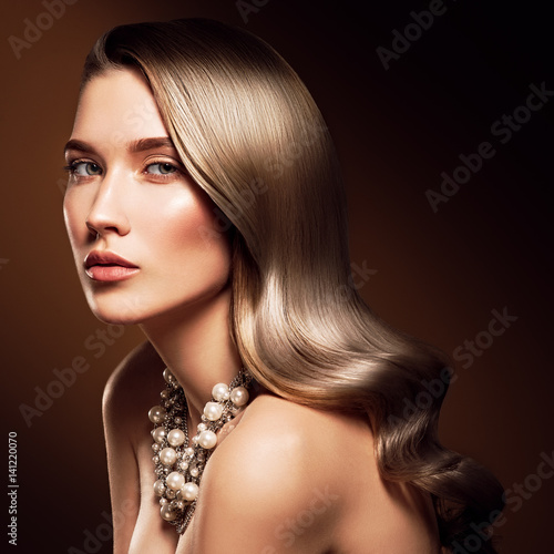 Plakat Brunetka kobieta z długim i lśniącym falistym włosy. Piękny model z kręcone fryzury