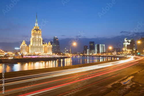 Spoed Foto op Canvas Canada Blurred night traffic movement lights at the center of Moscow, aerial urban view with Stalin Skyscraper and its reflection in the Moscow River, outdoor travel background