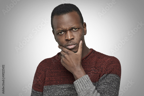 Photo  Close up portrait of serious puzzled African American male touching his chin, looking thoughtful and skeptical about something