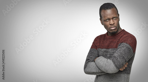 Studio portrait of skeptical African American young male in casual sweater looking with suspicious or annoyed expression, with hands folded on chest Wallpaper Mural