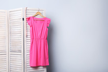 Pink Dress Hanging On Folding Screen On A Grey Background