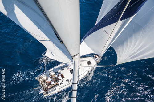 Fototapeta  Sailing boat with spinnaker from top of the mast, motion blurred sea