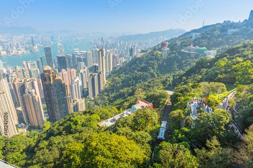 Plakat Widok z lotu ptaka popularnego szczytowego tramwaju od szczytu Victoria Peak, najwyższy szczyt wyspy Hong Kong, panoramę miasta w tle. Słoneczny dzień.