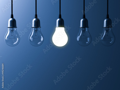 Fotografía  One hanging light bulb glowing different and standing out from unlit incandescent bulbs with reflection on dark blue background , leadership and different business creative idea concept