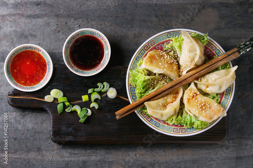 Gyozas potstickers on lettuce salad with sauces Canvas Print