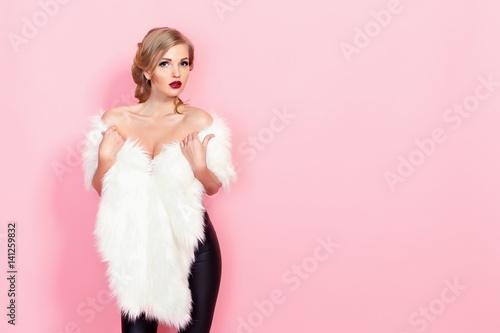 Fotografia Portrait of glam girl in white fur on pink background