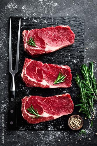 Fototapeta Raw meat, beef steak on black background, top view obraz na płótnie