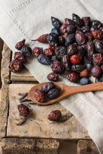 Dried Rose Hips Scattered On Wood Background Over Linen Cloth, Spoon With Fruits, By Window, Health Concept