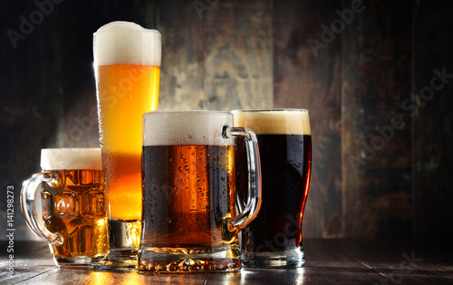 Tuinposter Alcohol Four glassed of beer on wooden background