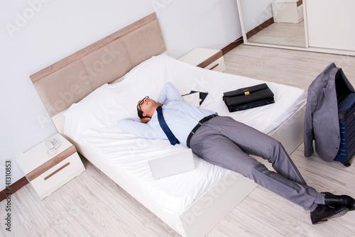 Plakat Biznesmen pracuje w pokoju hotelowym