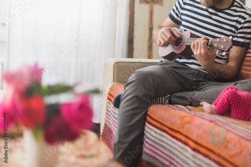 ragazzo suona chitarra sul divano
