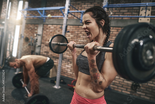 Foto auf AluDibond Fitness Fit couple lifting barbells in the gym.