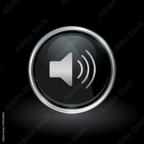 Fényképezés  Audio symbol with speaker volume icon inside round chrome silver and black button emblem on black background