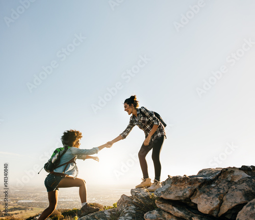 Fotografía  Female friends hiking help each other in mountains