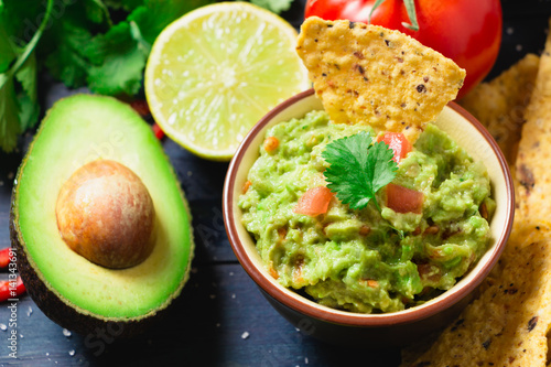 Guacamole with ingredients and tortilla chips