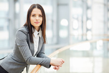 Portrait Of Beautiful Brunette Businesswoman Looking At Camera Leaning On Glass Railing In Modern Business Center