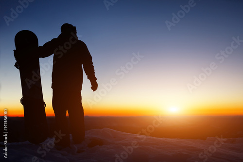 Garden Poster Brown Snowboard and ski concept with snowboarder on mountain top at sunset time. Space for text